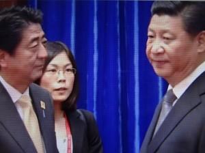 安倍さんは笑顔で接したのに近さんは能面だった(2014年11月、北京で握手をしたときの両者)